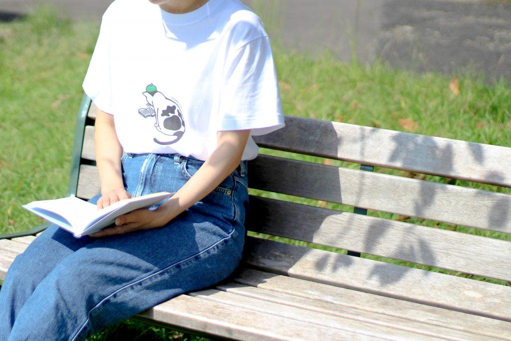 猫一Tシャツを着てベンチで読書