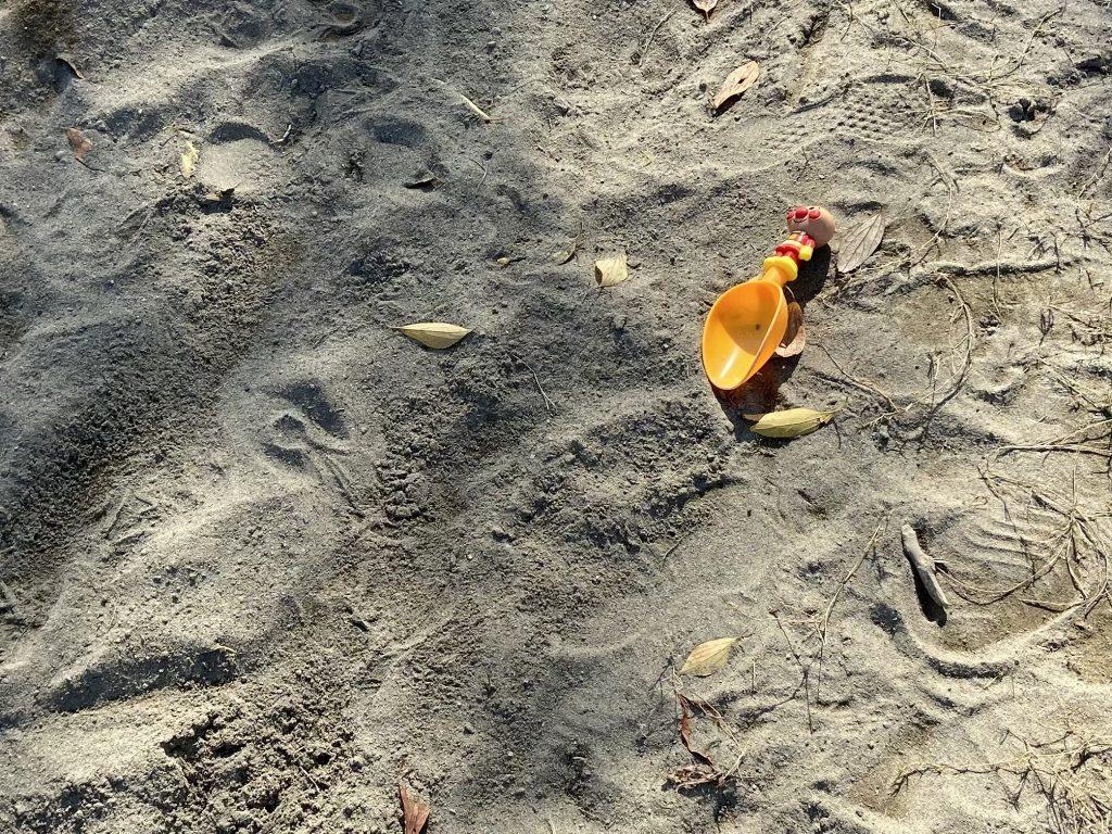 公園の砂場に、おもちゃのスコップが落ちているところ