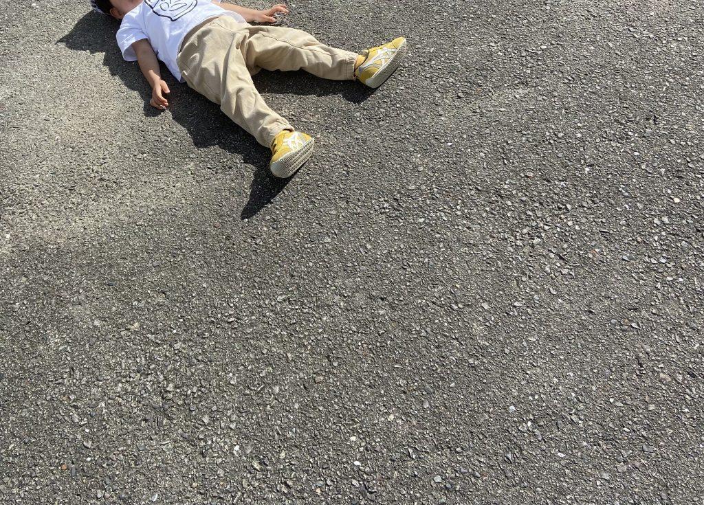 アスファルトの地面に転がっている子ども
